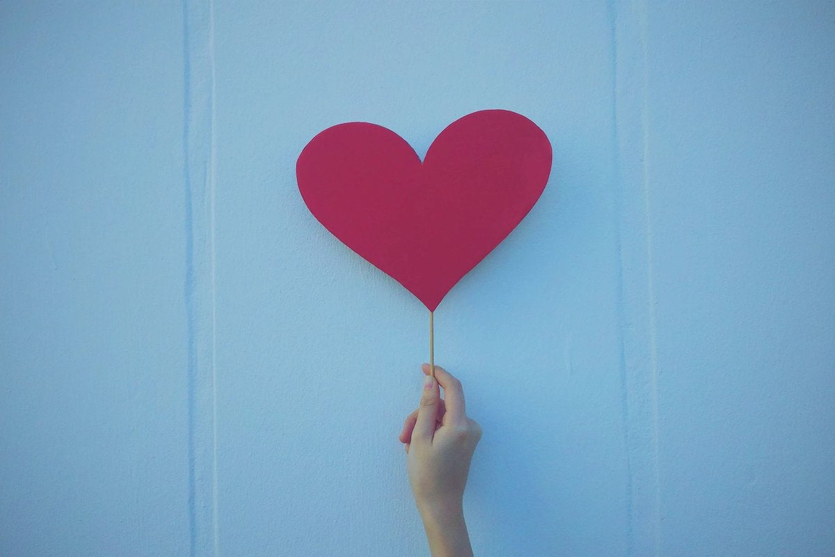 Paper heart on a stick held by a hand