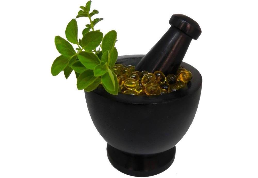 A black mortar and pestle with oregano softgels and oregano leaves on top.
