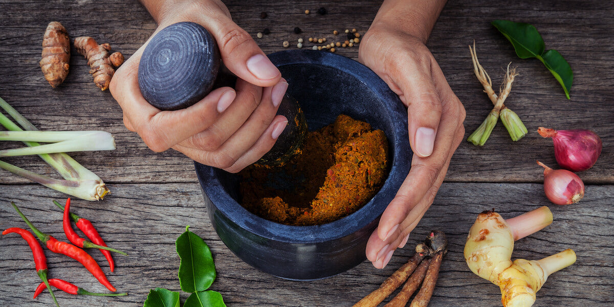 The same background of a mortar and pestle with 2 hands but facing the down.
