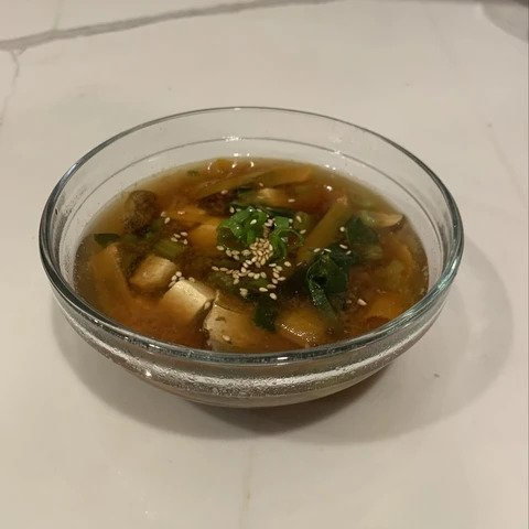 A bowl with miso soup ready to be served.