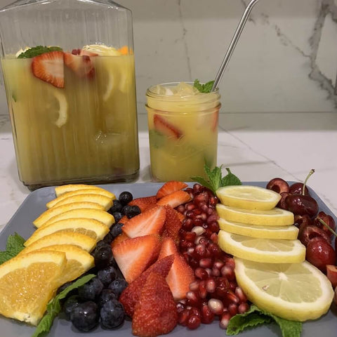A pitcher with yerba mate and fruits. The platter contains oranges, strawberries, lemons and other fruits.