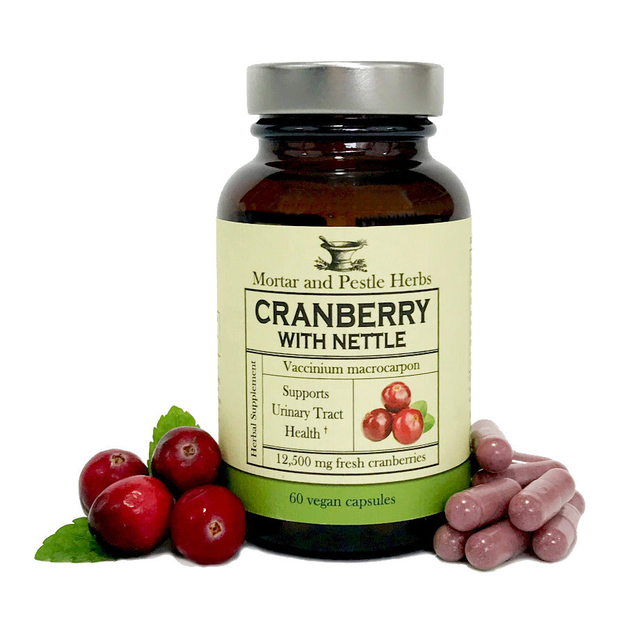 Cranberry with nettle label(Vaccinium macrocarpon), capsules and cranberries are surrounding the bottle.