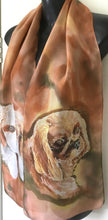 a golden King Charles spaniel on a rusty, tan and caramel hand painted silk scarf.