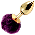 Small gold coloured metal butt plug with purple pompom tail. - Fetshop