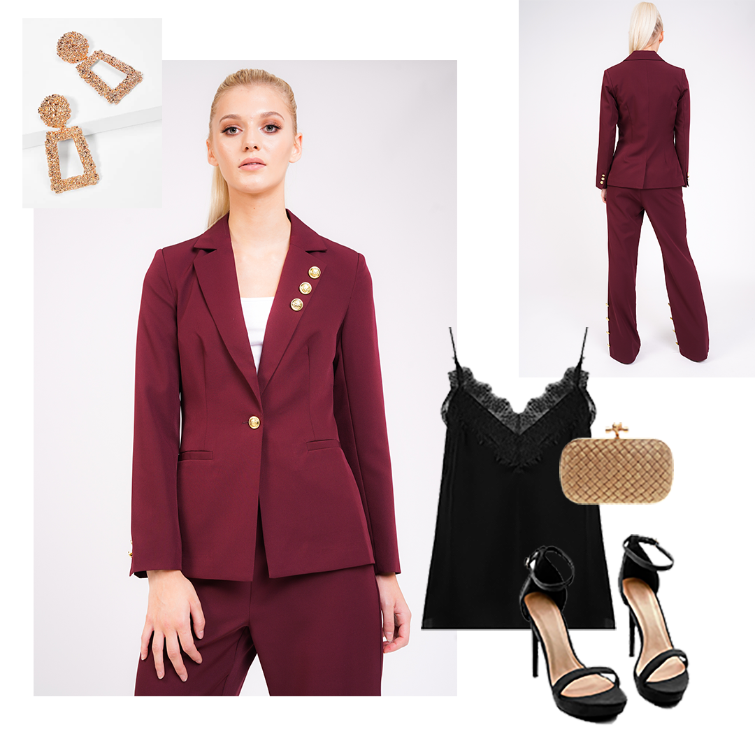 Model wears deep red tailored blazer and trouser suit with gold button detail on collar, cuff and front fastening