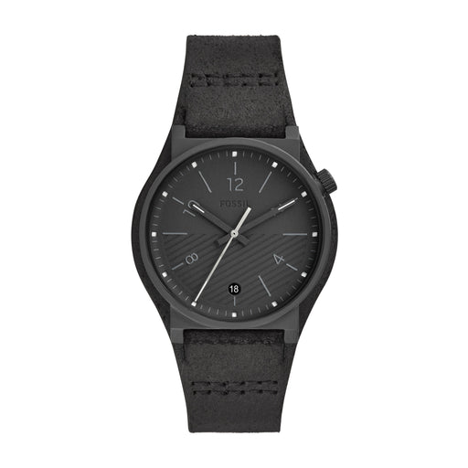 This all matte black ensemble has a few unique characteristics that sets it apart. The band is tapered shape and is made of a distressed leather material. The bezel is a very thin matte black that frames the uniquely designed dial. The bottom half of the watch is a subtle striped black and the hour markers are slim grey lines toward the center of the watch while only the even hours are marked with numerals. The hands are matching black and grey.