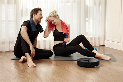 couple with sitting with robot vacuum
