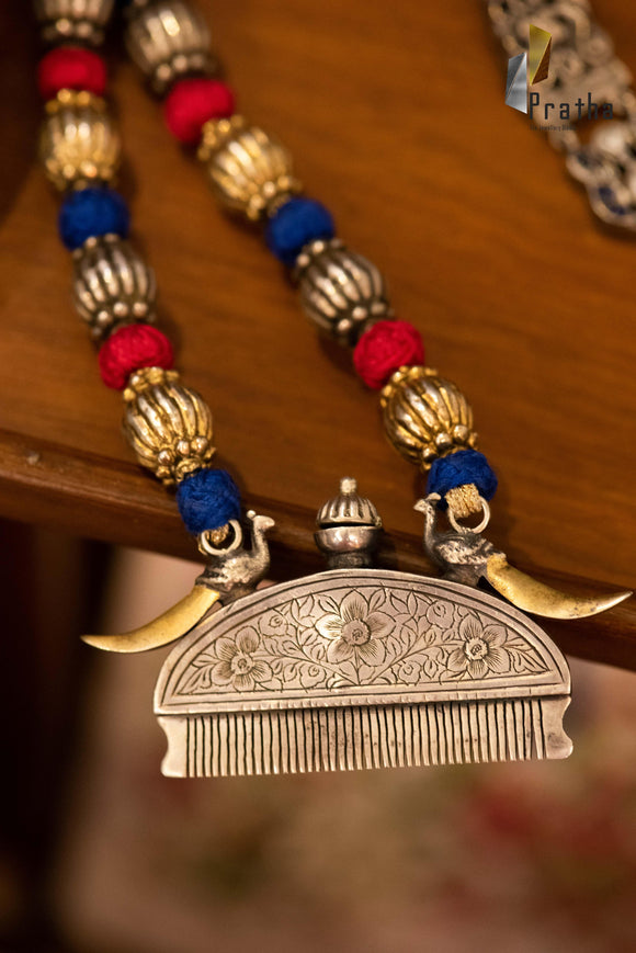 An ethnic comb pendant handcrafted in sterling silver with dual tone finish weaved in colourful thread work mala, a contemporary piece for a modern woman.