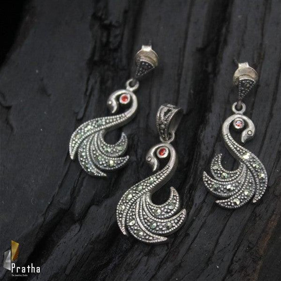 Intricately handcrafted in sterling silver with marcasites the swan pendant set with a hint of coloured stone will be a eye catcher piece.