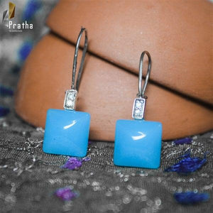 beautiful blue square stone earrings embellished with diamonds handcrafted in sterling silver with rhodium finish.