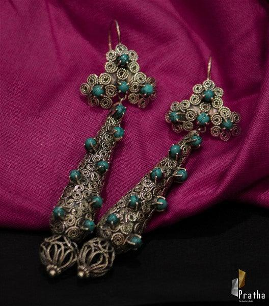 Sterling silver handcrafted long drop shape filigree work earrings embellished with synthetic turquoise stones .