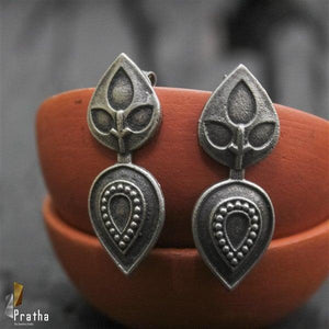 two differently designed leaf shape pieces attached together to form a unique earring handcrafted in sterling silver