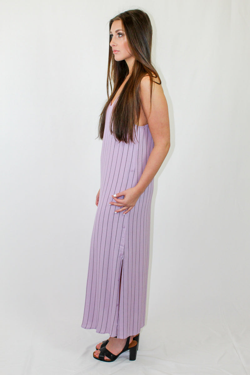 How To Wear: Get ready for Spring and Summer in the Amara Pinstripe Maxi Dress! With a sleek pinstripe print and side button up detailing, this maxi dress is best paired with sandals or wedges, a cute tan clutch and sun hat. The Details: Pinstripe maxi dress. Side button up details. Racerback. Color: Lavender...