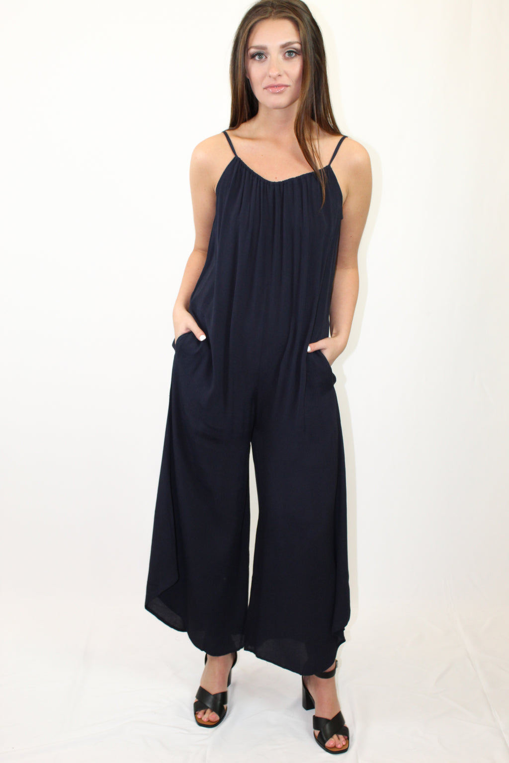 "How To Wear: Our favorite designer jumpsuit for the season! You will never be so comfortable, yet chic and on trend! With an adjustable neckline and pockets you will wish we had one in every color! Details: Runs generously. Recommend sizing down. High-low leg hemline. Model is 5'8"" and wearing a S."