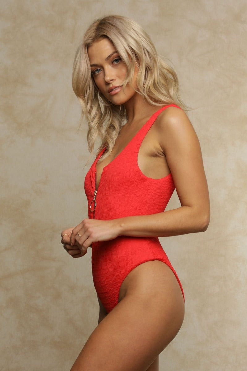 Babe-watch! The Ruby Smocking One-Piece Swimsuit is a fresh take on a classic! Featuring red smocking nylon spandex in a high cut with a scoop neck and low back and finished with a gold ring zipper pull on the front. Fully lined. Equally as cute as a bodysuit. Shop Fletch Ruby Smocking One Piece by Joelle Fletcher.
