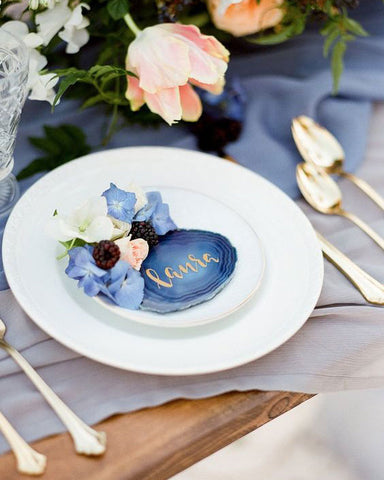 Agate place card holder with gold script. On top of white plate and light blue linen tablecloth. Gold cutlery and flowers.