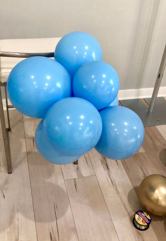 A stack of multiple light blue balloons tied together and tied to the post of a chair.