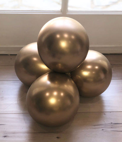 A stack of 4 gold balloons tied together.