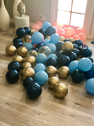 Dark and light blue, pink and gold balloons blown up laying on the floor.