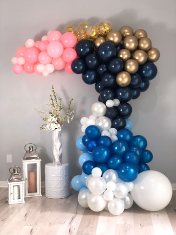 White, gold confetti, gold, light blue, dark blue and pink balloon garland against a gray wall.