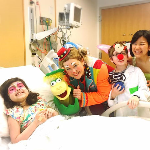 Group dressed up as cartoon characters visiting a sick child in the hospital