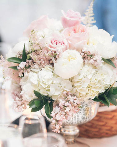 Pink and white floral bouquet or roses, hydrangeas and baby's breath in a silver vase.