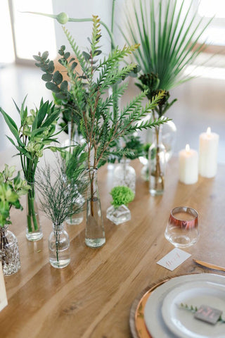 Eucalyptus, philodendron, ivy, monsteras,  ferns, chrysanthemums and fan palms  in various clear glass single-stemmed vases.