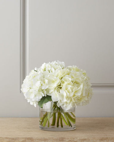 White hydrangea bouquet  in a short clear glass vase.