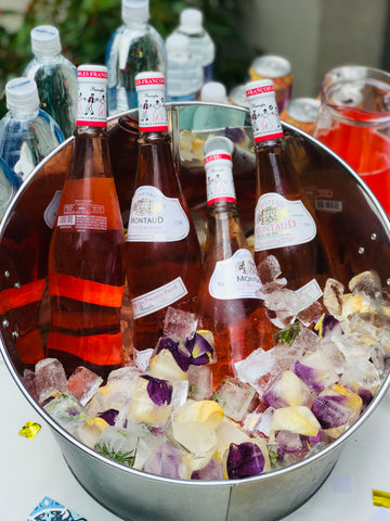 Rosé bottles in ice bucket with floral ice cubes.