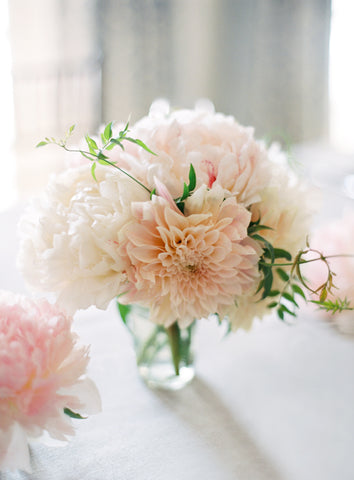 Peach peonies in a small clear glass vase.