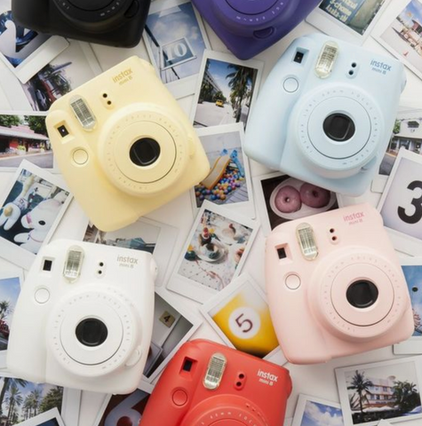 Various colors of polaroid cameras laying on top of polaroid pictures.