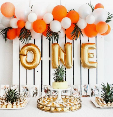 One year old birthday spread. Orange and white balloons decorated with pineapples and palm leaves.