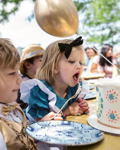 Little girl eating birthday cake. Dressed in Alice in Wonderland with party decor plates.