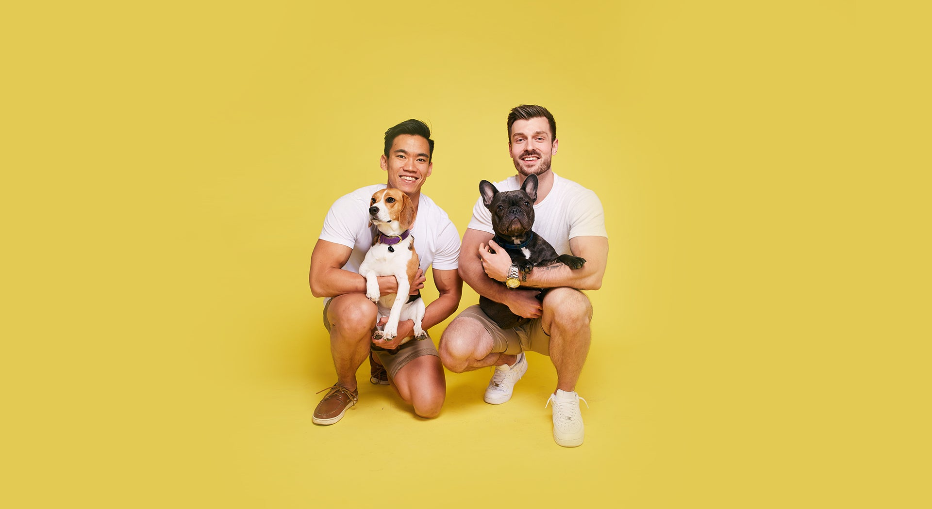 Chris and Damian holding two dogs
