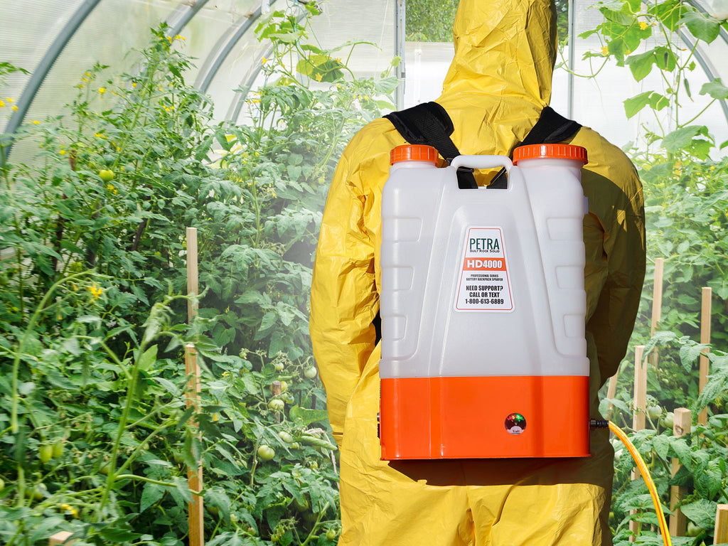 A man using a backpack sprayer to apply pesticides.