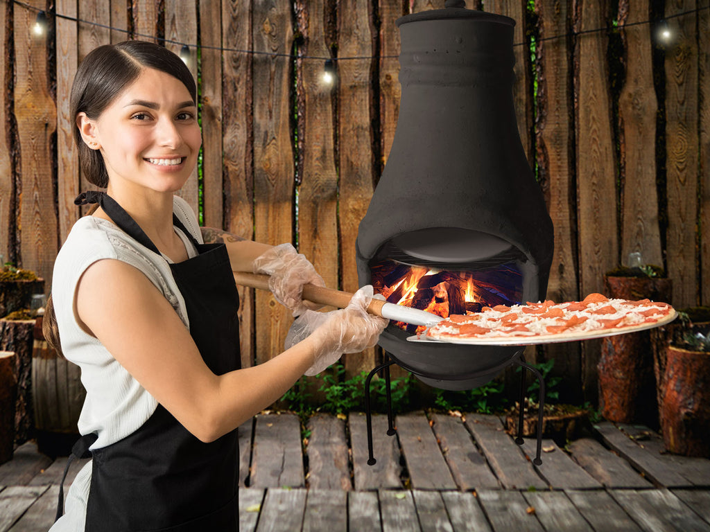 A woman holding a pan of pizza to cook in a wood-fired pizza oven.