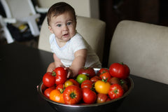 baby holding heirloom tomatoes