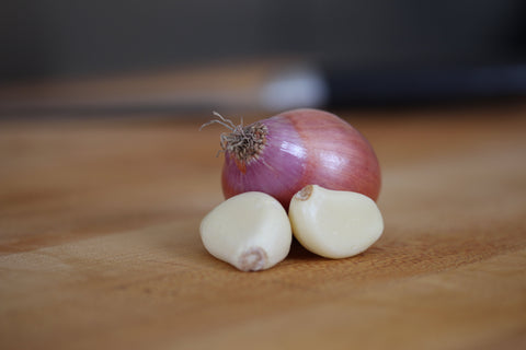 shallot and garlic cloves on cutting board