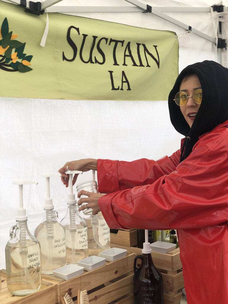 woman wearing red jacket refilling a glass bottle with hand soap at the farmers market