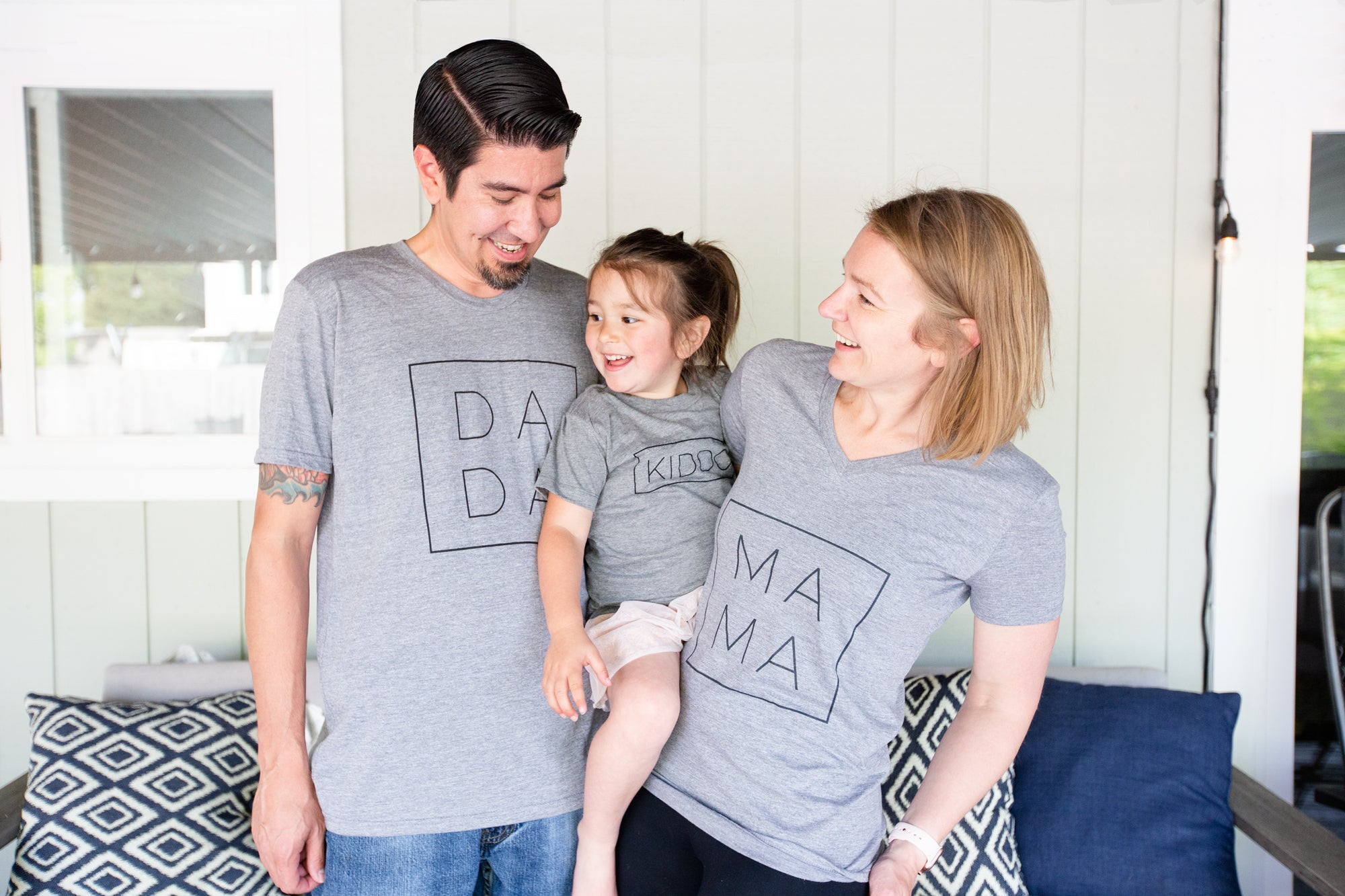 our happy family wearing shirts with Dada, Mama, and Kiddo printed in a modern font and square on grey matching shirts