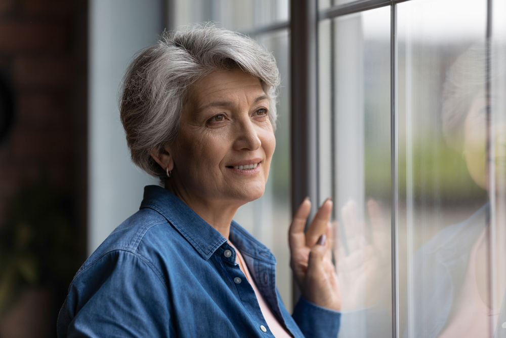 Lady looking through her new windows (Don't Void Your Window Warranty 5 Common Issues You Can Avoid)