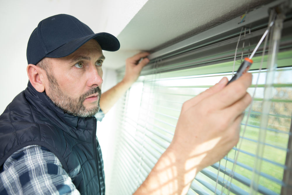 Man installing blinds and voiding warranty