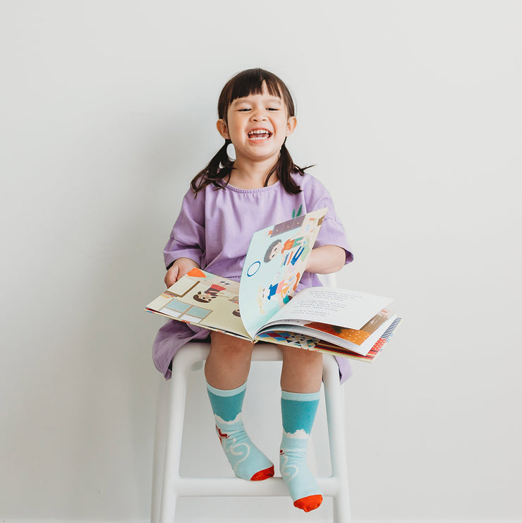 Little girl enjoying her Quinn's socks and book