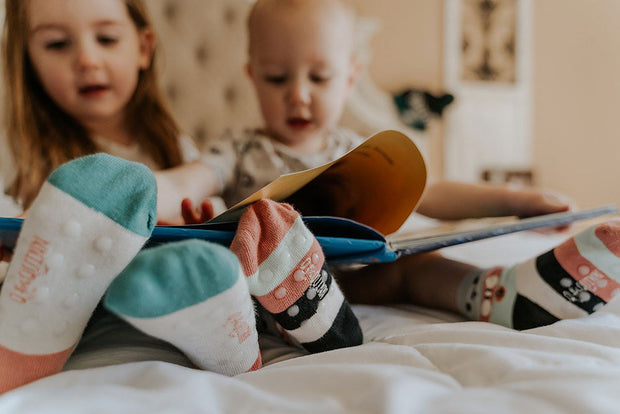 Baby and toddler reading a book in bed, wearing 'Arctic Animals' socks