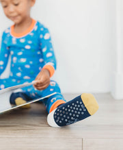 boy reading book wearing blue and yellow organic cotton socks
