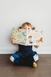 little girl reading book and wearing penguin tights | Q for Quinn