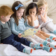 Children reading 'Quinn's Socks' book together while all wearing 'Quinn Cycles' Seamless socks