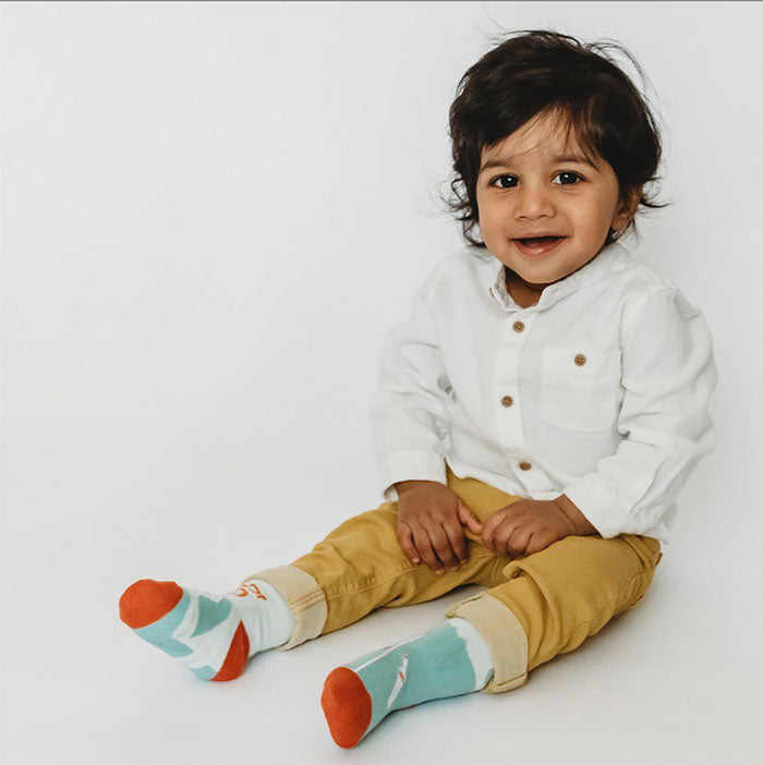 Little boy wearing 'Quinn's Sports' socks and smiling