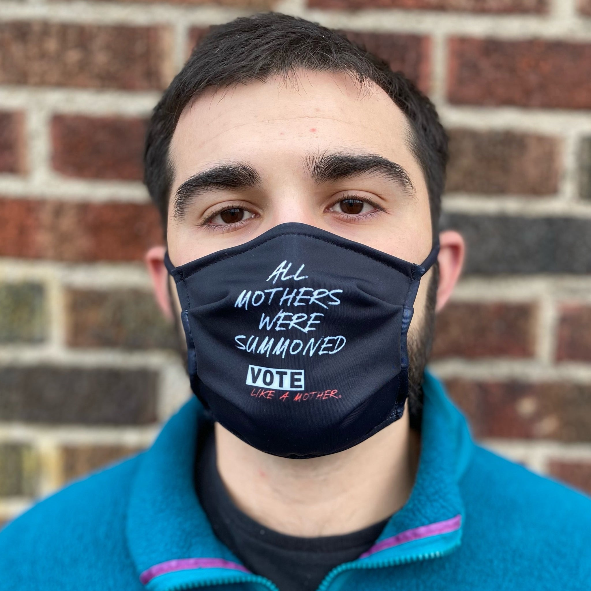 "A model with short hair and a beard sports the VLAM Summoned Mask which has a black background and white text that reads ""All Mothers Were Summoned"". Below the text is a graphic that says Vote Like a Mother. The person is wearing a teal fleece jacket zipped up over a black t-shirt and they stare into the camera calmly."