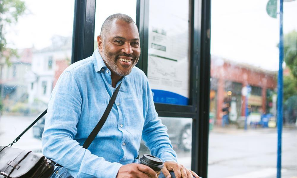 Smiling man sits at a bus stop